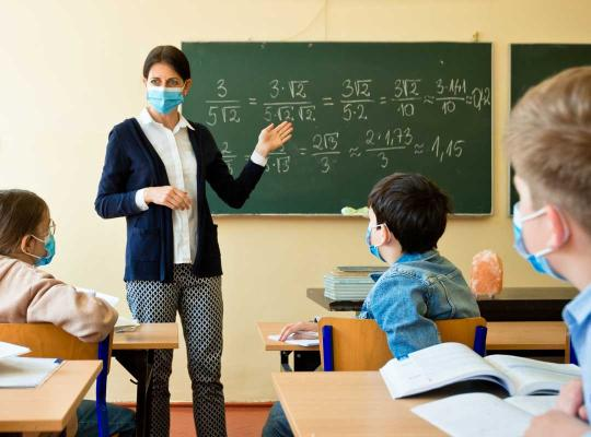 leerkracht met mondmsker geeft les